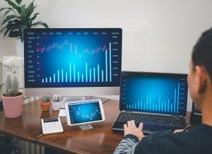 Joven interactuando con computadoras portátiles, teléfonos y tabletas con la plataforma de comercio de criptomonedas Bitcoin Buyer.