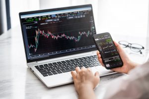 Hand holding smartphone with stock market data and using laptop display graph and chart for analyze and check before trading with Immediate Bitcoin app.