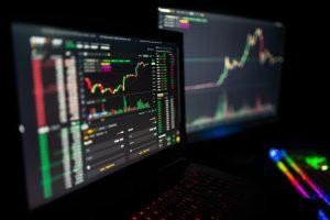 Un primo piano di due monitor che mostrano un trader di criptovalute che utilizza la piattaforma di trading Anon System